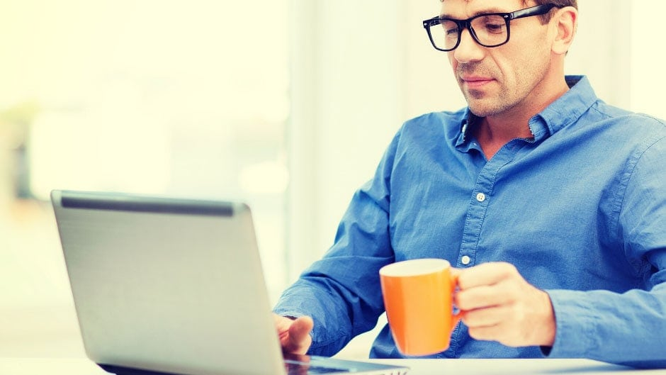 Man in blue shirt in front of laptop drinking coffee